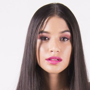 Model has straight long dark brown hair and is wearing pink eye-shadow and bright pink lipstick