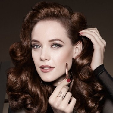 A woman looking into the camera whilst touching her thick, curly brown hair and holding a hair clip.