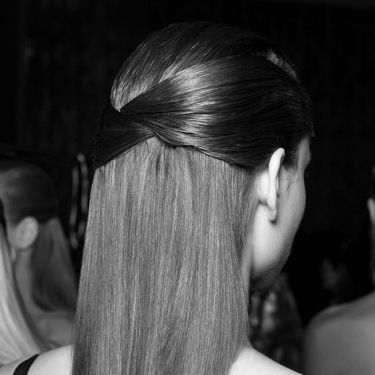 The sides of a model's hair are gathered up in a clip.