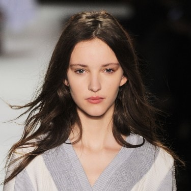 A model with long, dark brown hair on the runway, wearing a grey and white V-neck top