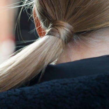 The back of a woman's head with a long blonde ponytail